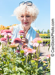 Portrait of a serene senior woman standing in the garden in a sunny day