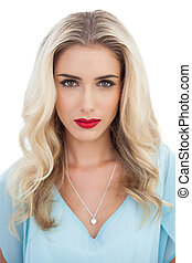 Portrait of a serious blonde woman in blue dress looking at camera on white background