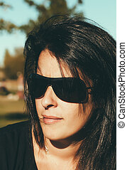 Portrait of a Serious Brunette Woman with Sunglasses