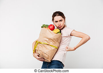 Portrait of a serious girl holding bag with groceries