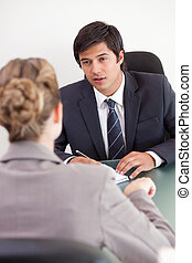 Portrait of a serious manager interviewing a female applicant