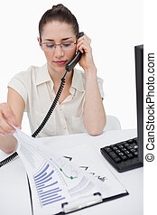 Portrait of a serious manager making a phone call while looking at statistics against a white background