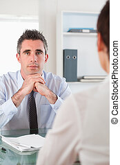 Portrait of a serious manager interviewing an applicant in...