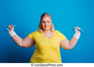 Portrait of a serious overweight woman with dumbbells in...