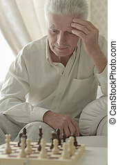 senior man playing chess