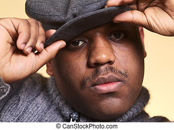 Portrait of a serious young man of African descent with a cap (Selective Focus, Focus on the right eye)