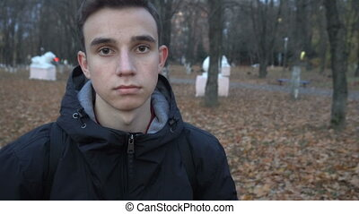 portrait of a serious young man standing in autumn Park