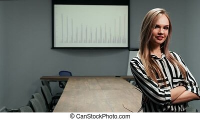 Portrait of a sexy blonde business woman in office clothes standing in the office against a large table and graphs on the screen looking at the camera