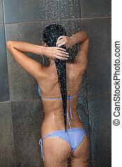 sexy young woman enjoying bath under water shower
