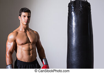 Portrait of a shirtless muscular boxer with punching bag