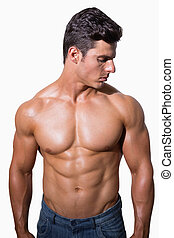 Portrait of a shirtless muscular man standing over white ...