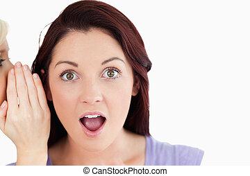 Portrait of a shocked women being told a secret in a studio