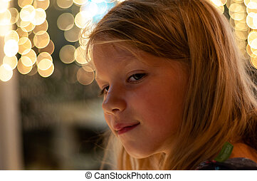 portrait of a six-year-old girl in profile against the background of lights