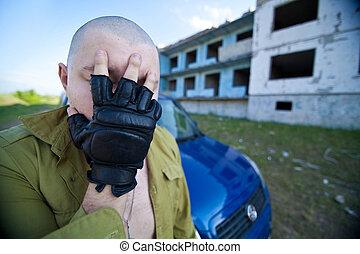 Portrait of a skinhead man near ruined building.