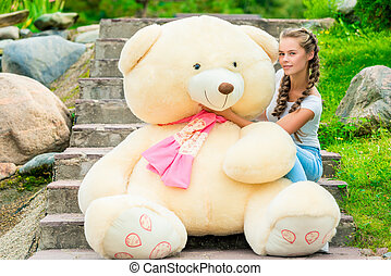 portrait of a slender girl with a huge teddy bear on the stairs in the park
