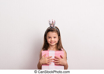 Portrait of a small girl with crown headband in studio, holding a wrapped box.