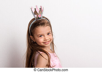 Portrait of a small girl with crown headband in studio on a white background.