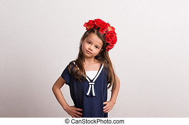Portrait of a small girl with flower headband in studio on a white background.
