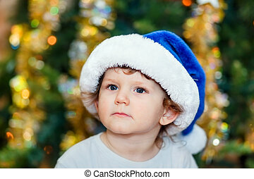 Portrait of a smart kid in a blue Santa hat, close-up on New Year's background bokeh.