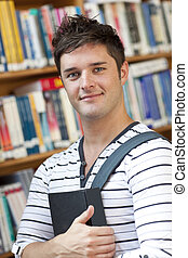 Portrait of a smart student holding a book standing in the library of his university