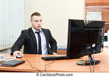 Portrait of a smart young businessman working on computer at office