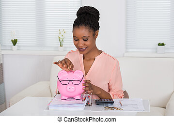 Woman Inserting Coin In Piggybank - Portrait Of A Smiling...
