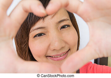 Portrait of a smiling asian girl with frame hands