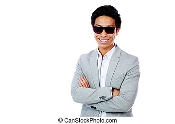 Portrait of a smiling asian man standing with arms folded over white background
