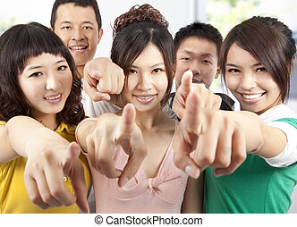 Portrait of a smiling asian students pointing at you