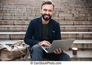 Portrait of a smiling attractive man working on laptop