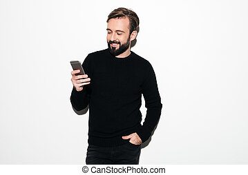 Portrait of a smiling bearded man texting on mobile phone