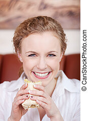 smiling blond woman eating wrap