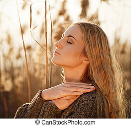 Portrait of a smiling blond woman relaxing outdoors in a autumn day
