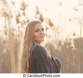 Portrait of a smiling blond woman smiling in a autumn day