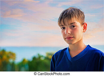 Portrait of a smiling boy against the sea at sunset