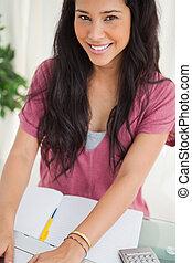 Portrait of a smiling brunette student using a laptop