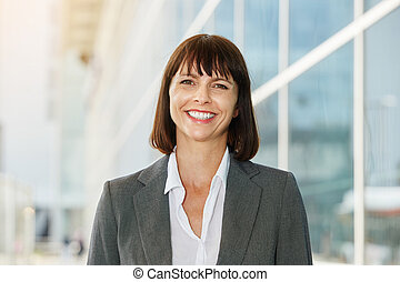 smiling business woman standing in the city