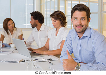 Portrait of a smiling businessman gesturing thumbs up with colleagues in meeting at the office