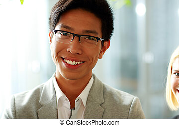 Portrait of a smiling businessman in glasses at office