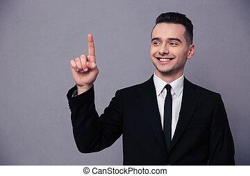 Portrait of a smiling businessman pointing finger up