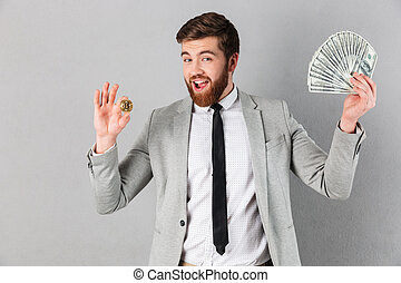 Portrait of a smiling businessman showing bitcoin