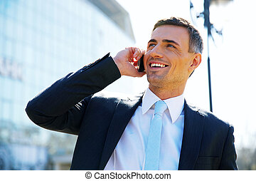 Portrait of a smiling businessman talking on the phone at street