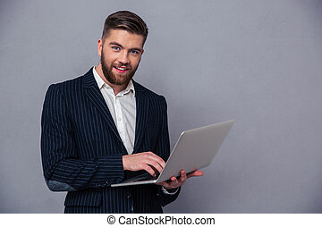 Portrait of a smiling businessman using lapto
