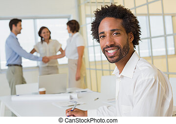 Portrait of a smiling businessman with colleagues hand shaking in background at the office