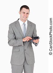 Portrait of a smiling businessman working with a calculator