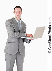 Portrait of a smiling businessman working with a laptop