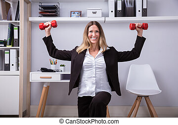 Businesswoman Doing Exercise With Dumbbell