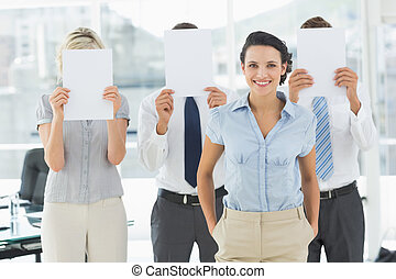 Portrait of a smiling businesswoman with colleagues holding blank paper in front of their faces in a bright office