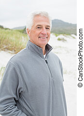 Portrait of a smiling casual senior man at beach