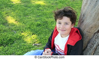 Portrait of a smiling child sitting on green grass